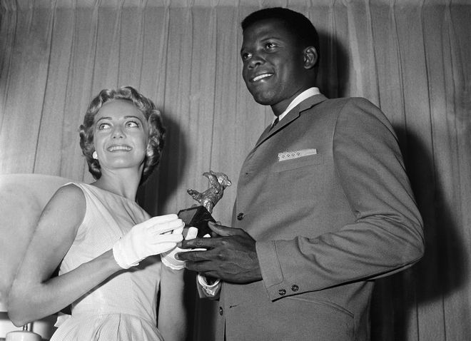 Miss Chicago (Andre Deckmann) presents the Silver Bear Award to Sidney Poitier, named as ?Best Actor of the Year? on Aug. 8, 1958 at the Berlin Film Festival for his performance in Stanley Kramer?s ?The Defiant Ones,? which will have its world premiere on Wednesday at the Roosevelt Theatre. With Chicago selected as the site of the world premiere, Miss Chicago was asked to stand in for the Berlin Festival Committee, since Poitier has been unavailable to go to Berlin to accept the award. Ceremonies took place on Friday in the Executive Suite of the Sherman Hotel. (AP Photo/CX)
