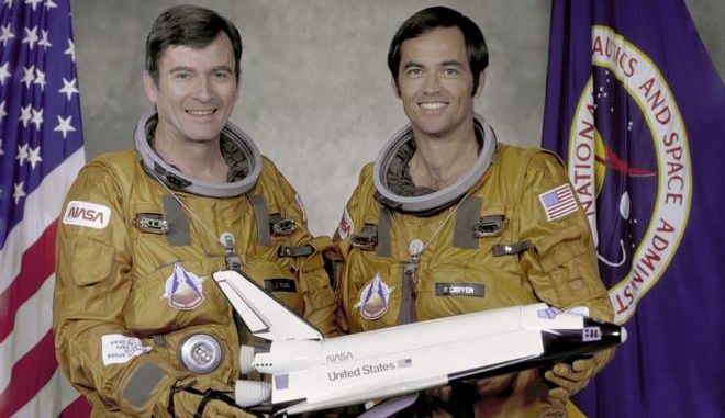 In this undated photo made available by NASA, STS-1 crew John Young, left, and Robert Crippen, hold a model of the space shuttle. NASA says Young, who walked on the moon and later commanded the first space shuttle flight, died on Friday, Jan. 5, 2018. He was 87 .(NASA via AP)