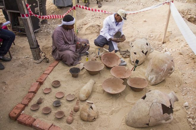 Egyptian excavation workers restore pottery near a new found in a tomb in Draa Abul Naga necropolis on Luxor's West Bank known as