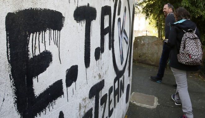 """People walk past graffiti reading """"ETA , Basque country and Freedom"""", in Sare, southwestern France, near Bayonne, Friday, April 7, 2017. The armed Basque separatist group ETA, inactive for more than five years, is to hand over its arms Saturday, a finishing touch to a 43-year violent campaign that claimed 829 lives, mostly in Spain. (AP Photo/Bob Edme)"""