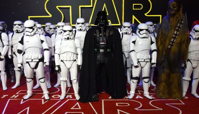 FILE - In this Dec. 16, 2015 file photo, characters from the file, including stormtroopers and Darth Vader pose for photographers upon arrival at the European premiere of the film 'Star Wars: The Force Awakens ' in London.  Turner networks TNT and TBS will be the exclusive basic-cable homes for all the Star Wars feature films, thanks to a multiyear deal with the films studios.  The deal, announced Wednesday, Sept. 14, 2016, includes the network premieres of last years Star Wars: The Force Awakens and the upcoming Rogue One: A Star Wars Story, opening in theaters in December.  (Photo by Jonathan Short/Invision/AP)