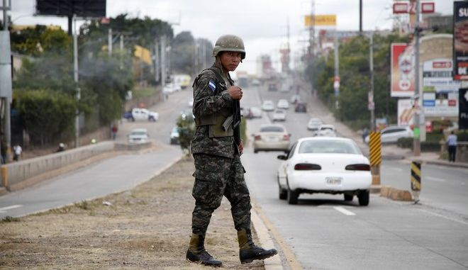 A soldier patrols a main road, during a 10-day curfew of 6 p.m. to 6 a.m. to quell demonstrations in Tegucigalpa, Honduras, Monday, Dec. 4, 2017. Tribunal president David Matamoros said 100 percent of the presidential election ballots had been tabulated, but the court was not declaring a winner yet, eight days after the election. (AP Photo/Fernando Antonio)