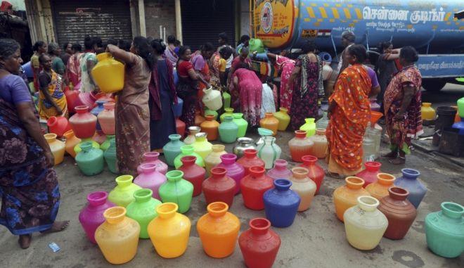 Κάτοικοι της Ινδίας περιμένουν στην μακριά ουρά για να γεμίσουν τα παγούρια τους με νερό από το φορτηγό που φέρνει νερό στην Τσενάι.