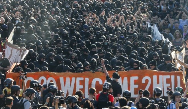 """Black dressed demonstrators attend a protest titled """"G20 Welcome to hell"""" against the G-20 summit in Hamburg, northern Germany, Thursday, July 6, 2017. The leaders of the group of 20 meet July 7 and 8. (AP Photo/Michael Probst)"""