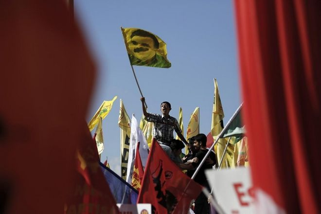 A Kurdish protester waving a flag which depict Abdullah Otsalan during a protest in Taksim square in Istanbul, Sunday, June 9, 2013. /               , ,  9  2013.