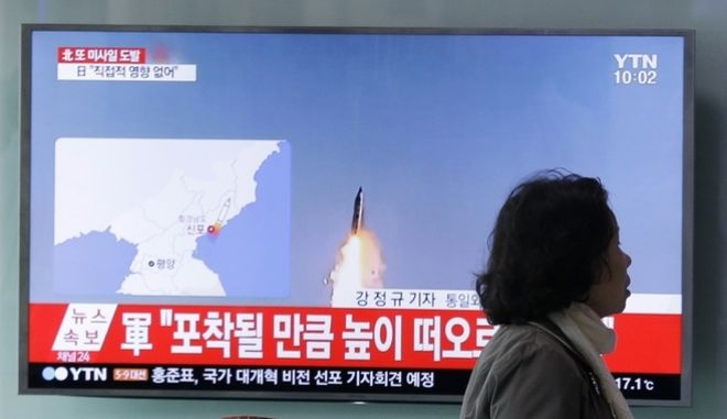 """A visitor walks by a TV showing file footage of a North Korea's ballistic missile launch, at Seoul Railway Station in Seoul, South Korea, Sunday, April 16, 2017. A North Korean missile exploded during launch Sunday from the country's east coast, U.S. and South Korean officials said, a high-profile failure that comes as a powerful U.S. aircraft carrier approaches the Korean Peninsula in a show of force. The letters on the top read """"North Korea fired a missile."""" (AP Photo/Ahn Young-joon)"""