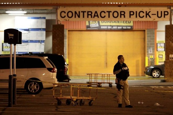 A police officer stands near a vehicle, left, inside a perimeter in the parking lot of a Home Depot store, Tuesday, Oct. 31, 2017, in Passaic, N.J. Police investigating a rented Home Depot truck's deadly rampage down a bike path near New York's World Trade Center have surrounded the white Toyota minivan with Florida plates parked in the lot. (AP Photo/Julio Cortez)
