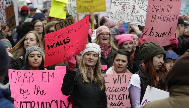 Marchers carry signs during a Women's March, Saturday, Jan. 20, 2018, in Seattle. On the anniversary of President Donald Trumps inauguration, people participating in rallies and marches in the U.S. and around the world Saturday denounced his views on immigration, abortion, LGBT rights, women's rights and more. (AP Photo/Ted S. Warren)