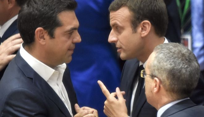 Greek Prime Minister Alexis Tsipras, left, speaks with French President Emmanuel Macron, second left, during a round table meeting at an EU summit in Brussels on Thursday, June 22, 2017. European Union leaders are gathering for a two day summit to weigh measures in which to tackle terrorism and migration and to create closer defense ties. (John Thys, Pool Photo via AP)