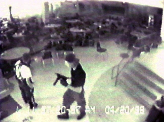 Eric Harris, left, and Dylan Klebold, carrying a TEC-9 semi-automatic pistol, are pictured in the cafeteria at Columbine High School, in Littleton, Colorado, during their April 20, 1999 shooting rampage where they killed a teacher and 12 students.  Both gunmen killed themselves later in the school library. This still image is from a videotape released by the Jefferson County Sheriff's Department. Jefferson County District Judge Brooke Jackson ordered the tapes released late last month, along with copies of law-enforcement radio transmissions. The releases were requested by the families of slain students Kelly Fleming and Daniel Rohrbough, who have sued the sheriff's office.  (AP Photo/Jefferson County Sheriff's Department) NO SALES