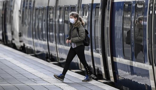 A woman with a face mask leaves a train at the main station in Muenster, western Germany, Thursday, April 30, 2020. To fight the coronavirus pandemic, Germany ordered social distancing, mandatory face masks when shopping and in public transport. (AP Photo/Martin Meissner)