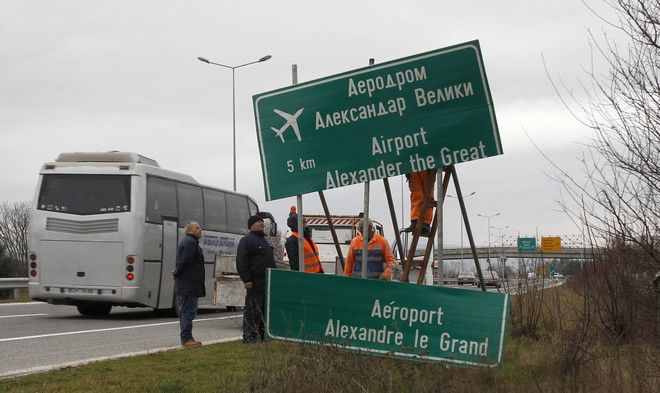 Workers remove a road sign for the airport near Macedonia's capital Skopje, on Saturday, Feb. 24, 2018. The Macedonian government decided recently to rename the country's main airport which carried the name of the ancient warrior king Alexander the Great, as Skopje International Airport, in a goodwill gesture toward neighboring Greece. (AP Photo/Boris Grdanoski)