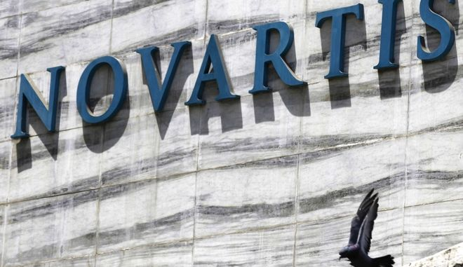 FILE - In this April 1, 2013 file photo, a dove flies near the logo of Novartis India Limited at their head office in Mumbai, India. Colombias government announced on Tuesday, May 17, 2106, that it is giving pharmaceutical giant Novartis a few weeks to lower prices on a popular cancer drug or see its monopoly on production of the medicine broken and competition thrown open to generic rivals. (AP Photo/Rafiq Maqbool, File)