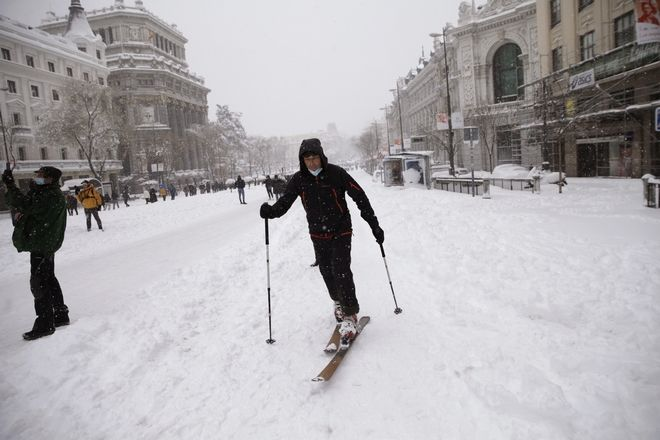 A man skis during a heavy snowfall in downtown Madrid, Spain, Saturday, Jan. 9, 2021. A persistent blizzard has blanketed large parts of Spain with 50-year record levels of snow, halting traffic and leaving thousands trapped in cars or in train stations and airports that suspended all services as the snow kept falling on Saturday. (AP Photo/Andrea Comas)
