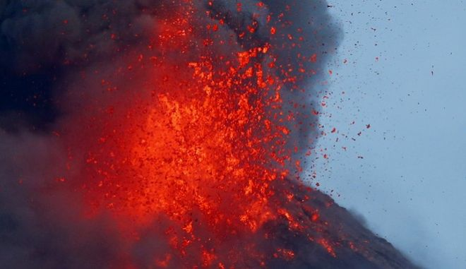 In this Thursday, Jan. 25, 2018, file photo, the Mayon volcano spews molten lava during its sporadic eruption early as seen from a village in Legazpi city, Albay province, around 340 kilometers (200 miles) southeast of Manila, Philippines. (AP Photo/Bullit Marquez, File)
