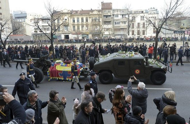 People watch the motorcade with the coffin of the late Romanian King Michael during the funeral ceremony in Bucharest, Romania, Saturday, Dec. 16, 2017. Tens of thousands of Romanians joined the European royals on Saturday to pay their respects to late King Michael as a state funeral got underway. Michael, who ruled Romania twice before being forced to abdicate by the communists in 1947, died at the age of 96 in Switzerland this month. (AP Photo/Andreea Alexandru)