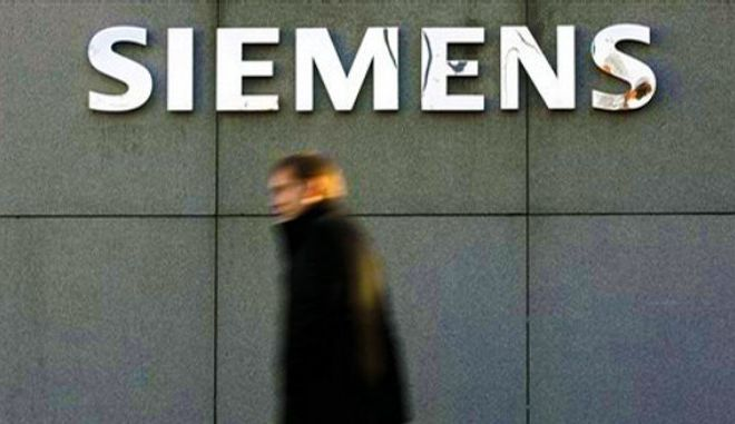 ** FILE ** A man passes a Siemens logo at the Siemens Forum building in Munich, southern Germany, in this  Dec. 13, 2006 file picture. The trial of the first Siemens AG ex-manager accused of embezzling millions of euros (dollars) in the high-profile corruption scandal that rocked the company last year is to open next month, a Munich court said Wednesday, April 9, 2008. (AP Photo/Christof Stache)