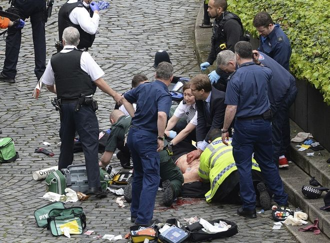 """Conservative Member of Parliament Tobias Ellwood, centre, helps emergency services attend to an injured person outside the Houses of Parliament, London, Wednesday, March 22, 2017. London police say they are treating a gun and knife incident at Britain's Parliament """"as a terrorist incident until we know otherwise."""" The Metropolitan Police says in a statement that the incident is ongoing. It is urging people to stay away from the area. Officials say a man with a knife attacked a police officer at Parliament and was shot by officers. Nearby, witnesses say a vehicle struck several people on the Westminster Bridge. (Stefan Rousseau/PA via AP)."""