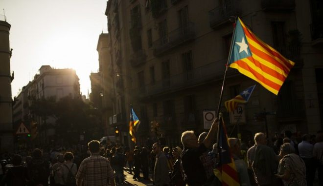 "People wave ""esteladas"", Catalonian independence flags, in Barcelona, Friday, Oct. 27, 2017. In one of the most momentous days in recent Spanish history, Spain fired Catalonia's regional government and dissolved its parliament Friday after a defiant Catalan declaration of independence that flouted the country's constitution. (AP Photo/Francisco Seco)"