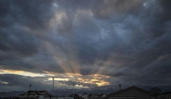 Ακτίνες φωτός βγαίνουν μέσα από τα σύννεφα πάνω από την πόλη των Τρικάλων καθώς ο ήλιος δύει πίσω από την οροσειρά του Κόζιακα
