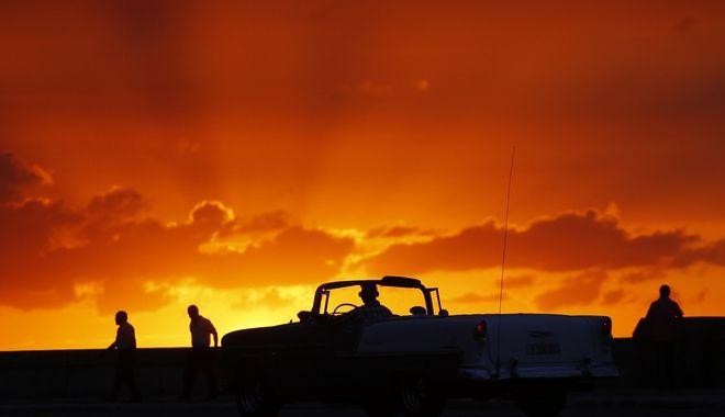 Ένας άνδρας οδηγεί ένα κλασικό αμερικανικό αυτοκίνητο στον αυτοκινητόδρομο στη Μαλεκόν, στην Αβάνα, το ηλιοβασίλεμα