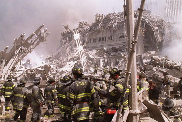 Firefighters work to sift through debris following the collapse of the World Trade Center in a terrorist attack. A hijacked American Airlines Boeing 767, originating from Boston's Logan Airport, struck 1 World Trade Center (north tower) at 8:45 a.m. At 9:03 a.m., a United Airlines 767, also hijacked in Boston, crashed into 2 World Trade Center (south tower). Both towers later collapsed.