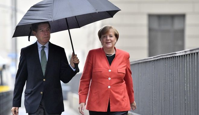 German Chancellor Angela Merkel, right, and her husband Joachim Sauer arrive to cast their vote in Berlin, Germany, Sunday, Sept. 24, 2017. Merkel is widely expected to win a fourth term in office as Germans go to the polls to elect a new parliament. (AP Photo/Martin Meissner)