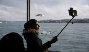 Γυναίκα φωτογραφίζεται με τη βοήθεια selfie stick, σε πλοιάριο στην θάλασσα του Μαρμαρά, στην Κωνσταντινούπολη