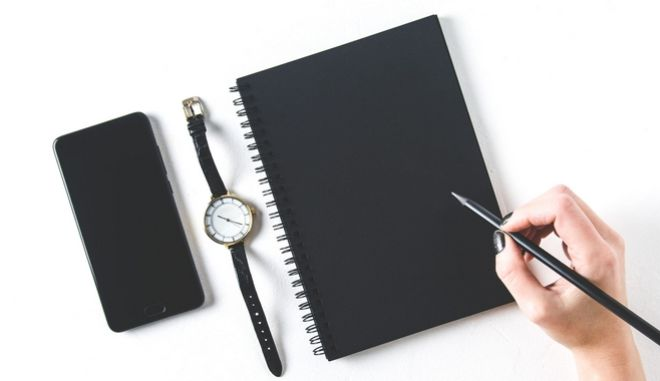 Black Notepad and mobile phone on white background