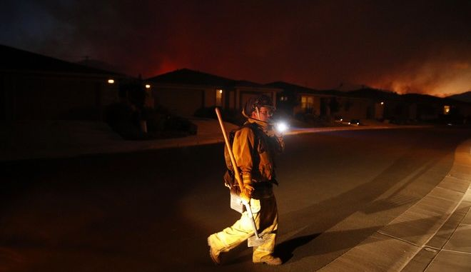 A firefighter looks for flammable items in an evacuated residential area as wildfires continue to burn Saturday, Oct. 14, 2017, in Santa Rosa, Calif.  Fire officials have ordered mandatory evacuations. (AP Photo/Jae C. Hong)