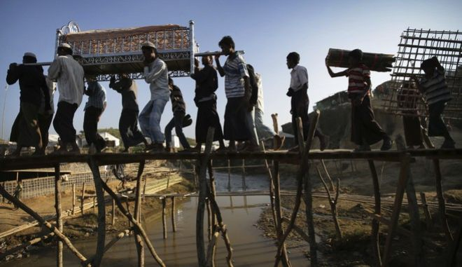 Rohingya Muslim men carry the body to a cemetery in Kutupalong refugee camp on Sunday, Nov. 26, 2017, in Bangladesh. Since late August, more than 620,000 Rohingya have fled Myanmar's Rakhine state into neighboring Bangladesh, where they are living in squalid refugee camps. (AP Photo/Wong Maye-E)
