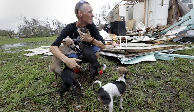 Sam Speights tries to hold back tears while holding his dogs and surveying the damage to his home in the wake of Hurricane Harvey, Sunday, Aug. 27, 2017, in Rockport, Texas. Speights tried to stay in his home during the storm but had to move to other shelter after his home lost its roof and back wall. (AP Photo/Eric Gay)