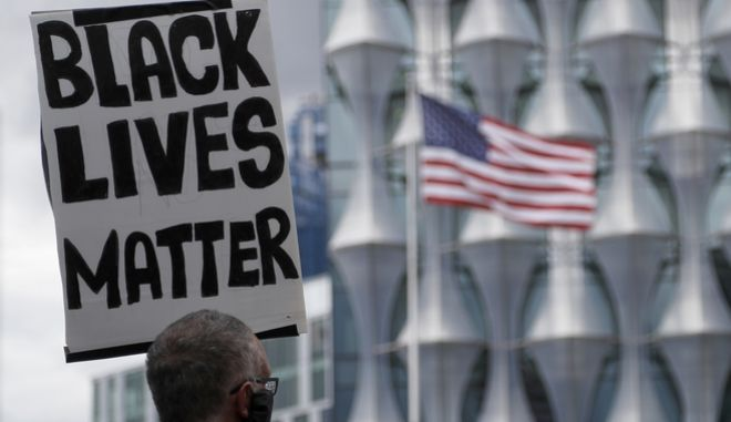 """Διαδηλωτής κρατάει πλακάτ που γράφει """"Black Lives Matter"""""""