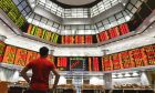 A man watches trading boards at a private stock market gallery in Kuala Lumpur, Malaysia, Friday, Feb. 9, 2018. Asian stocks plunged Friday after Dow Jones industrials on Wall Street plummeted more than 1,000 points, deepening a week-long sell-off. (AP Photo/Sadiq Asyraf)