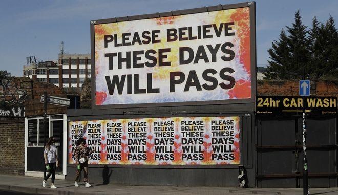 Γυναίκες με μάσκες μπροστά από μήνυμα ελπίδας σε διαφημιστική πινακίδα