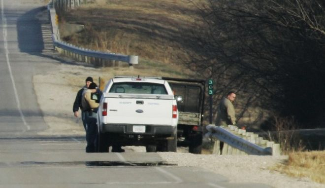 Law enforcement officers look over the scene where searchers found a body along U.S. 54 near Toronto, Kan., Thursday, Nov. 29, 2007. A body found in Kansas appears to be that of a missing college student who led a secret life as an Internet porn star, police said Thursday. (AP Photo/Orlin Wagner)