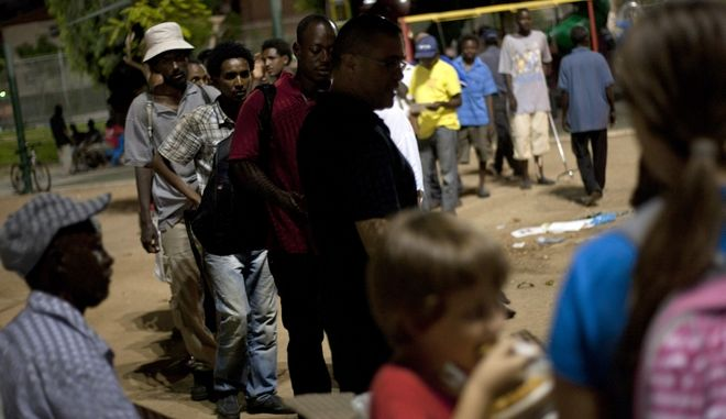 African migrants wait in line for free food in Tel Aviv, Israel,Thursday, Aug. 30, 2012. A senior official says Israel will start rounding up thousands of unauthorised Sudanese migrants and put them in a detention centre if they don't leave the country voluntarily. Interior Minister Eli Yishai says the detentions will begin in mid-October. Israel is grappling with an unanticipated influx of 60 000 migrants from Africa, including 15 000 from Sudan. The government insists most came to find better lives, not asylum. Most are from Sudan and Eritrea, states with repressive regimes. Israel cannot expel them to their homelands because it has signed an international refugee treaty that bars it from forcibly returning migrants to countries considered liable to persecute them. (AP Photo/Ariel Schalit)