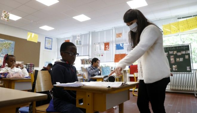 A teacher wears a protective face mask during a class as part of the visit of French President Emmanuel Macron's visit to the Pierre Ronsard elementary school Tuesday, May 5 2020 in Poissy, outside Paris. Starting from May 11, all French businesses will be allowed to resume activity and schools will start gradually reopening. (Ian Langsdon, Pool via AP)