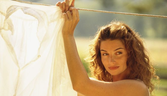 Woman hanging laundry on clothesline outdoors