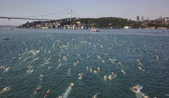 Competitors swim in the Bosphorus strait during the Bosporus Cross-Continental Swimming Race, in Istanbul, Sunday, July 23, 2017. Over 2,000 open-water competitors plunged into the water from a ferry docked on the city's Asian side and swam from Asia to Europe across Istanbul's Bosphorus Strait for about 6.5km in this cross-continental event. (Ali Aksoyer /DHA-Depo Photos via AP)