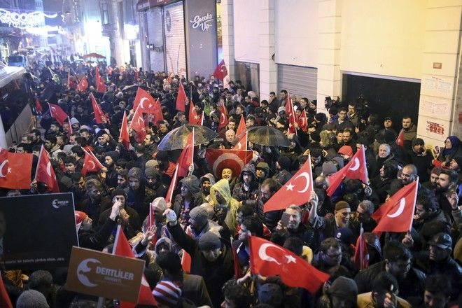 """Supporters of Turkey's President Recep Tayyip Erdogan wave flags outside the Dutch consulate to protest, in Istanbul, early Sunday, March 12, 2017. Turkey and the Netherlands sharply escalated a dispute between the two NATO allies on Saturday as the Dutch withdrew landing permission for the Turkish foreign minister's aircraft, drawing Turkish President Recep Tayyip Erdogan to call them """"fascists"""". (AP Photo)"""