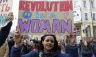 """Φεμινίστρια διαδηλώτρια κρατάει πανό που γράφει """"Η επανάσταση είναι γυναίκα"""", Ουκρανία"""