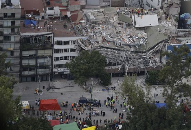 Rescue workers search for people trapped inside a collapsed building in the Roma Norte neighborhood of Mexico City, Wednesday, Sept. 20, 2017. Mexicans across the city are digging through collapsed buildings, trying to save people trapped in debris under schools, homes and businesses, toppled by a 7.1 earthquake that killed more than 200 people. (AP Photo/Rebecca Blackwell)