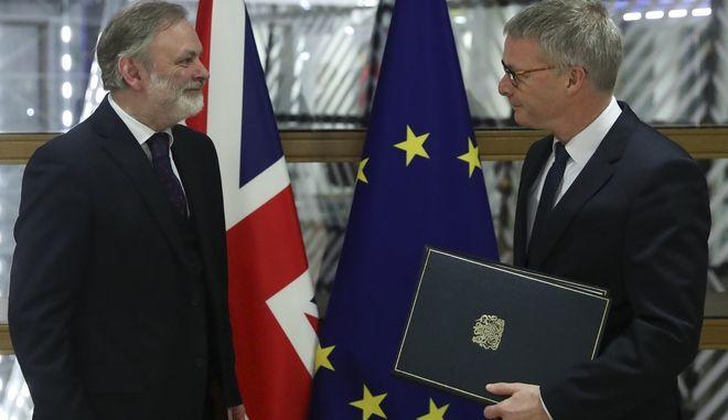Ο Sir Tim Barrow, Μόνιμος Αντιπρόσωπος του Ηνωμένου Βασιλείου στην ΕΕ, αριστερά, παραδίδει τα μέσα επικύρωσης στον Γενικό Γραμματέα του Ευρωπαϊκού Συμβουλίου Jeppe Tranholm-Mikkelsen
