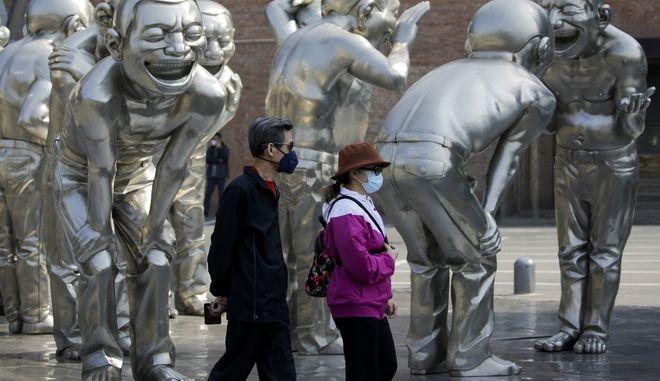 Ζευγάρι με μάσκες μπροστά από γκαλερί στην Κίνα