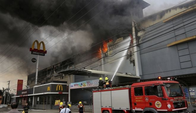 Firemen battle a fire that rages at a shopping mall, Saturday, Dec. 23, 2017, in Davao city, southern Philippines. The fire which still raging for hours now have trapped an undetermined number of people, fire officials said. (AP Photo/Manman Dejeto)