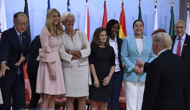 """US President Donald Trump, 2nd right, jokes as his daughter Ivanka Trump, 2nd left, poses with participants of the panel discussion """"Launch Event Women's Entrepreneur Finance Initiative"""" on the second day of the G-20 summit in Hamburg, Germany, Saturday, July 8, 2017. (Patrik Stollarz/Pool Photo via AP)"""