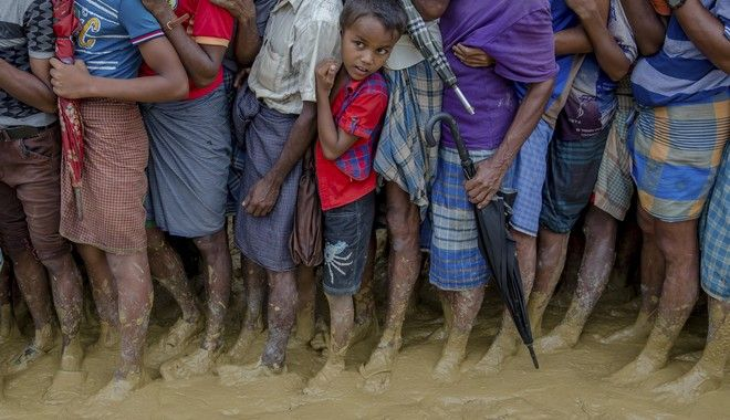 A young Rohingya Muslim boy, who crossed over from Myanmar into Bangladesh, waits alongwith others for his turn to collect food aid near Kutupalong refugee camp, Bangladesh, Tuesday, Sept. 19, 2017. With a mass exodus of Rohingya Muslims sparking accusations of ethnic cleansing from the United Nations and others, Myanmar leader Aung San Suu Kyi on Tuesday said her country does not fear international scrutiny and invited diplomats to see some areas for themselves. (AP Photo/Dar Yasin)