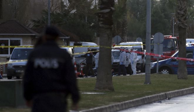 Security and medics at the explosion site in Izmir, Turkey, Thursday, Jan. 5, 2017. An explosion believed to have been caused by a car bomb in front of a courthouse in the western Turkish city of Izmir on Thursday wounded several people, a local official said. Two of the suspected attackers were killed in an ensuing shootout with police. (AP Photo/Emre Tazegul)