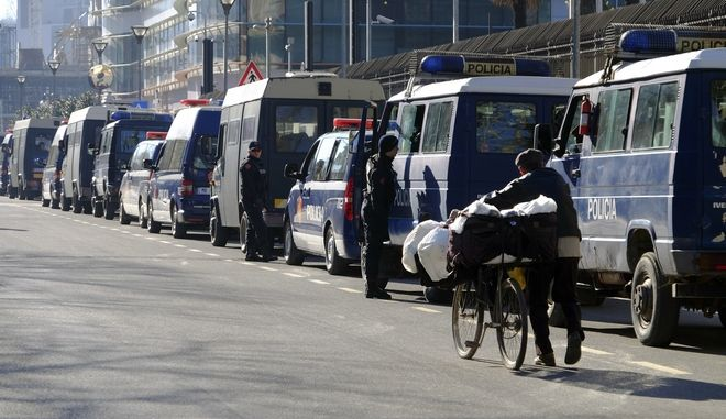 An Albanian man carrying his belongings on a bicycle passes by a convoy of police vehicles near the main square in Albania, Tirana, Saturday, Jan. 27, 2018, where Albania's opposition is to hold an anti-government protest. The protest is accusing the Cabinet of links to organized crime and calling for its resignation. (AP Photo/Hektor Pustina)